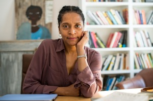 Emily Bernard faces the camera, seated at a table, with one hand touching her face. A wall of bookshelves and a painting of a Black woman are in soft focus behind her.