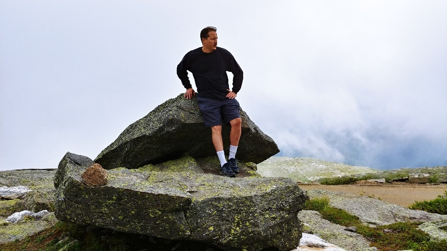 Malcom Greene oudoors, standing on a large rock, leaning against another large rock, looking to the left.